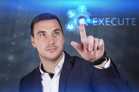 execute: Business, Technology, Internet and network concept. Young businessman working on a virtual screen of the future and sees the inscription: Execute