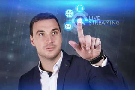 keywords link: Business, Technology, Internet and network concept. Young businessman working on a virtual screen of the future and sees the inscription: Live streaming