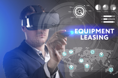 keywords link: Business, Technology, Internet and network concept. Young businessman working in virtual reality glasses sees the inscription: Equipment leasing Stock Photo