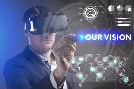 keywords link: Business, Technology, Internet and network concept. Young businessman working in virtual reality glasses sees the inscription: Our vision Stock Photo