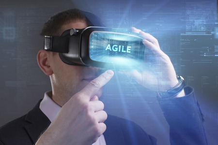 keywords link: Business, Technology, Internet and network concept. Young businessman working in virtual reality glasses sees the inscription: Agile Stock Photo