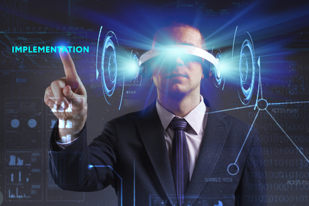 keywords link: Business, Technology, Internet and network concept. Young businessman working in virtual reality glasses sees the inscription: Implementation