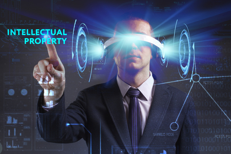keywords link: Business, Technology, Internet and network concept. Young businessman working in virtual reality glasses sees the inscription: Intellectual property Stock Photo
