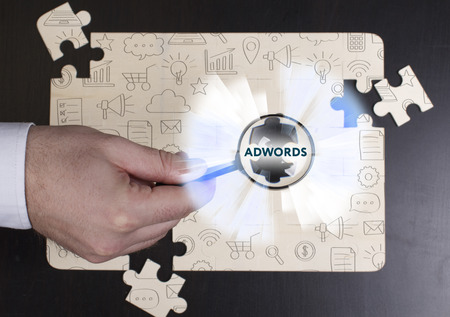 adwords: Business, Technology, Internet and network concept. Young businessman shows the word: AdWords