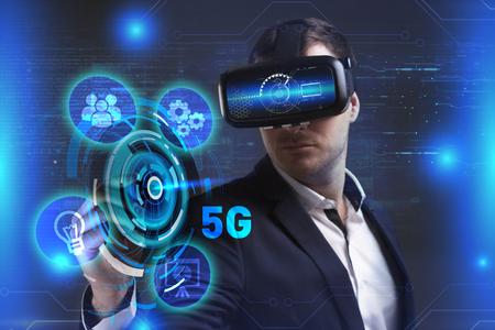 Concetto di business, tecnologia, Internet e rete. Il giovane uomo d'affari che lavora in vetri di realtà virtuale vede l'iscrizione: 5G Archivio Fotografico - 78605333