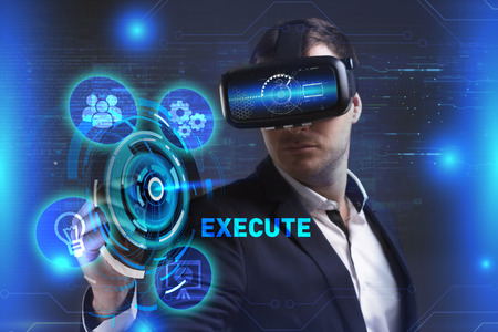 execute: Business, Technology, Internet and network concept. Young businessman working in virtual reality glasses sees the inscription: Execute Stock Photo