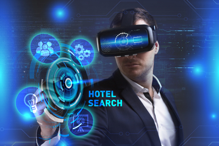 Business, Technology, Internet and network concept. Young businessman working in virtual reality glasses sees the inscription: Hotel search