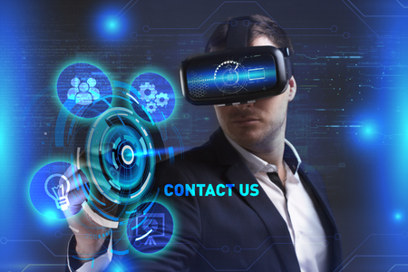 Business, Technology, Internet and network concept. Young businessman working in virtual reality glasses sees the inscription: Contact us