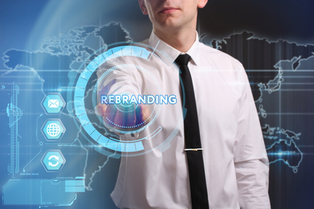 keywords link: Business, Technology, Internet and network concept. Young businessman working on a virtual screen of the future and sees the inscription: Rebranding
