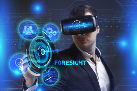 Business, Technology, Internet and network concept. Young businessman working in virtual reality glasses sees the inscription: Foresight Stock Photo
