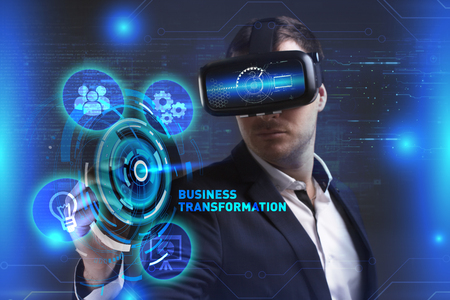 Business, Technology, Internet and network concept. Young businessman working in virtual reality glasses sees the inscription: Business transformation