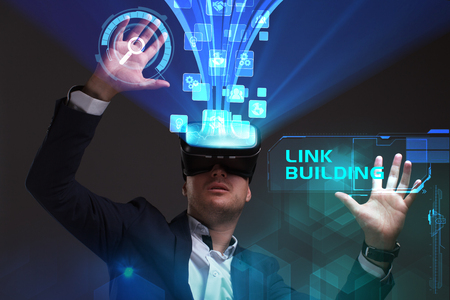 Business, Technology, Internet and network concept. Young businessman working in virtual reality glasses sees the inscription: Link building Stock Photo