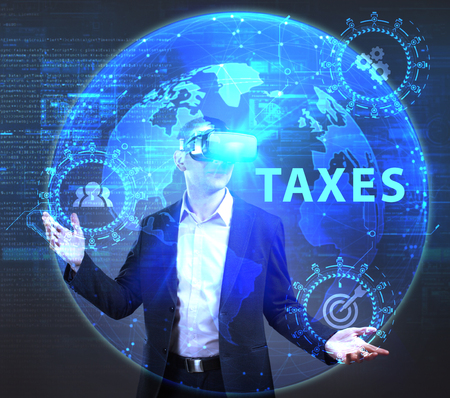 The concept of business, technology, the Internet and the network. A young entrepreneur working on a virtual screen of the future and sees the inscription: Taxes Stock Photo