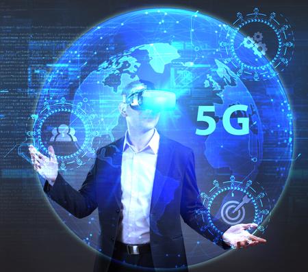 ビジネス、技術、インターネット、ネットワークのコンセプトです。未来の仮想画面に取り組んでいる若い起業家と碑文を見ている: 5 G 写真素材