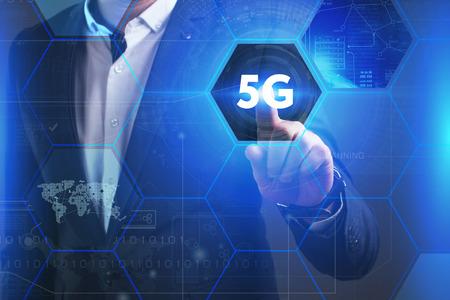 ビジネス、技術、インターネット、ネットワークのコンセプトです。未来の仮想画面に取り組んでいる青年実業家と碑文を見ている: 5 G 写真素材
