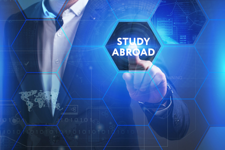 queries: Business, Technology, Internet and network concept. Young businessman working on a virtual screen of the future and sees the inscription: Study abroad