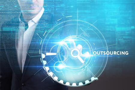 ビジネス、技術、インターネット、ネットワークのコンセプトです。未来の仮想画面に取り組んでいる青年実業家と碑文を見ている: アウトソーシン