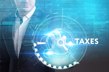 Business, Technology, Internet and network concept. Young businessman working on a virtual screen of the future and sees the inscription: Taxes