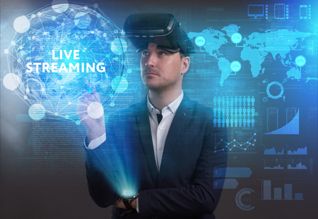 keywords: Business, Technology, Internet and network concept. Young businessman working on a virtual screen of the future and sees the inscription: Live streaming