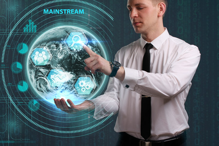 Business, Technology, Internet and network concept. Young businessman working on a virtual screen of the future and sees the inscription: Mainstream Stock Photo