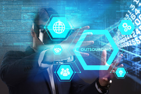 Business, Technology, Internet and network concept. Young businessman working in virtual reality glasses sees the inscription: Outsourcing Stock Photo