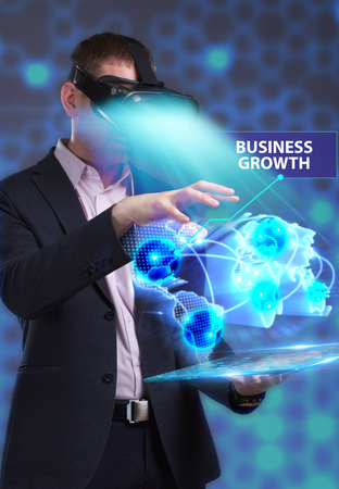 niche: Business, Technology, Internet and network concept. Young businessman working in virtual reality glasses sees the inscription: Business growth Stock Photo
