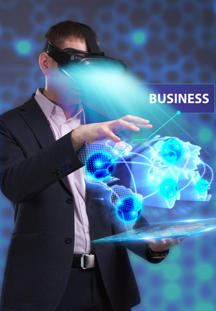 niche: Business, Technology, Internet and network concept. Young businessman working in virtual reality glasses sees the inscription: Business