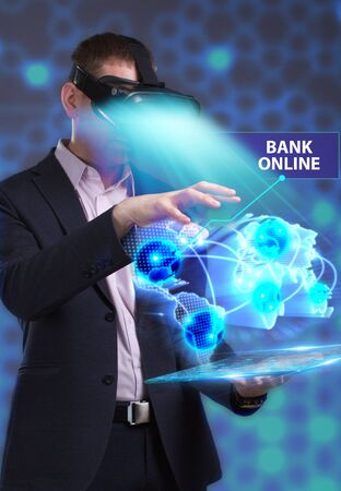 Business, Technology, Internet and network concept. Young businessman working in virtual reality glasses sees the inscription: Bank online Stock Photo
