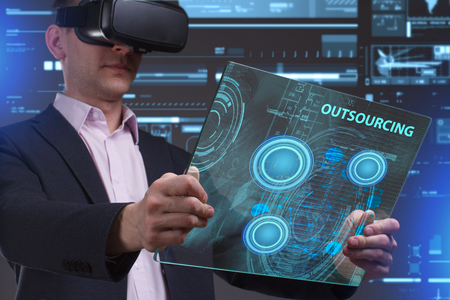 niche: Business, Technology, Internet and network concept. Young businessman working in virtual reality glasses sees the inscription: Outsourcing Stock Photo