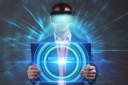 niche: Business, Technology, Internet and network concept. Young businessman working in virtual reality glasses sees the inscription: Regulation Stock Photo