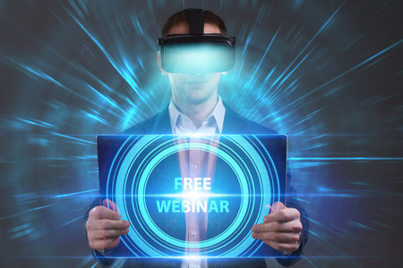 niche: Business, Technology, Internet and network concept. Young businessman working in virtual reality glasses sees the inscription: Free webinar