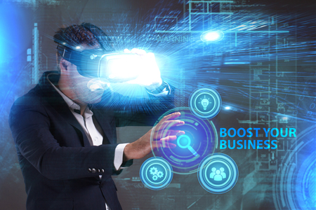 niche: Business, Technology, Internet and network concept. Young businessman working in virtual reality glasses sees the inscription: Boost your business Stock Photo