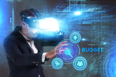 niche: Business, Technology, Internet and network concept. Young businessman working in virtual reality glasses sees the inscription: Budget