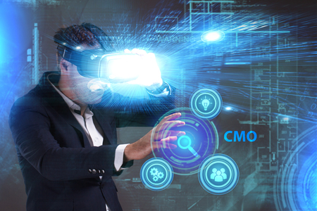 niche: Business, Technology, Internet and network concept. Young businessman working in virtual reality glasses sees the inscription: CMO