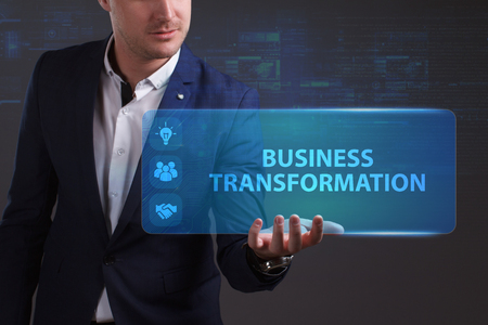 niche: Business, Technology, Internet and network concept. Young businessman working on a virtual screen of the future and sees the inscription: Business transformation