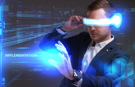 seo: Business, Technology, Internet and network concept. Young businessman working in virtual reality glasses sees the inscription: Implementation