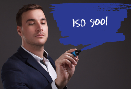 seo: The concept of business, technology, the Internet and the network. Young businessman showing inscription: ISO 9001