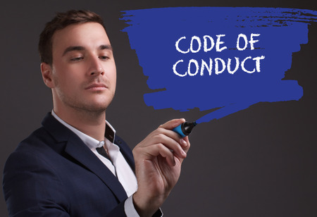 seo: The concept of business, technology, the Internet and the network. Young businessman showing inscription: Code of conduct