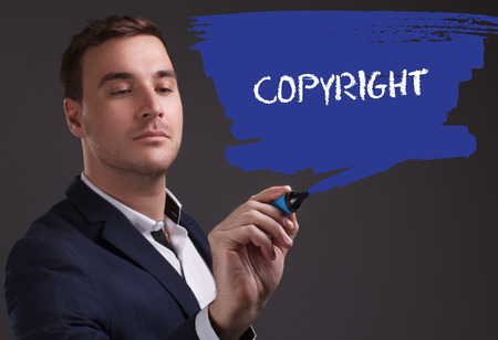seo: The concept of business, technology, the Internet and the network. Young businessman showing inscription: Copyright