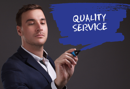 seo: The concept of business, technology, the Internet and the network. Young businessman showing inscription: Quality service Stock Photo