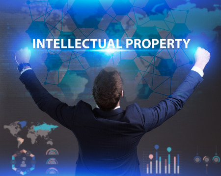 The concept of business, technology, the Internet and the network. Young businessman showing inscription: Intellectual property