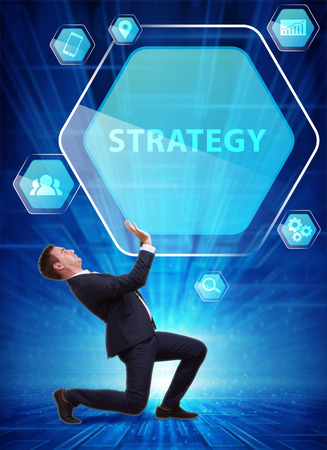 Business, Technology, Internet and network concept. Young businessman working on a virtual screen of the future and sees the inscription: Strategy