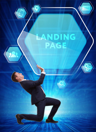 Business, Technology, Internet and network concept. Young businessman working on a virtual screen of the future and sees the inscription: Landing page Stock Photo