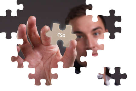 The concept of business, technology, the Internet and the network. A young businessman collects a puzzle with the proper inscription: CSO