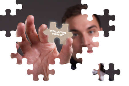 The concept of business, technology, the Internet and the network. A young businessman collects a puzzle with the proper inscription: Intellectual property