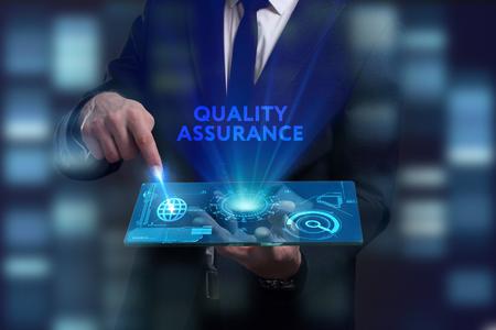 Bedrijfs-, technologie-, internet- en netwerkconcept. Jonge zakenman werken aan een virtueel scherm van de toekomst en ziet het opschrift: Kwaliteitsborging