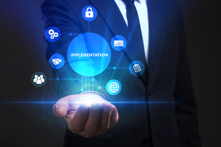 keywords: Business, Technology, Internet and network concept. Young businessman working on a virtual screen of the future and sees the inscription: Implementation