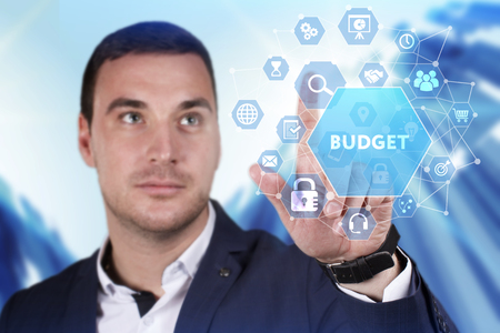 Business, Technology, Internet and network concept. Young businessman working on a virtual screen of the future and sees the inscription: Budget Stock Photo
