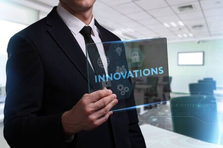 Business, Technology, Internet and network concept. Young businessman working on a virtual screen of the future and sees the inscription: Innovations