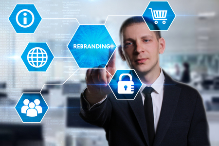 Business, Technology, Internet and network concept. Young businessman working on a virtual screen of the future and sees the inscription: Rebranding